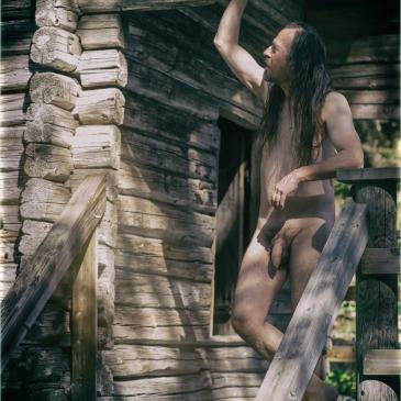 nackter Mann auf der Veranda einer Holzhütte