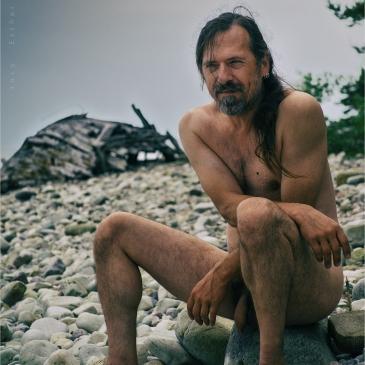 nackter mann am kiesstrand, im hintergund ein wrack