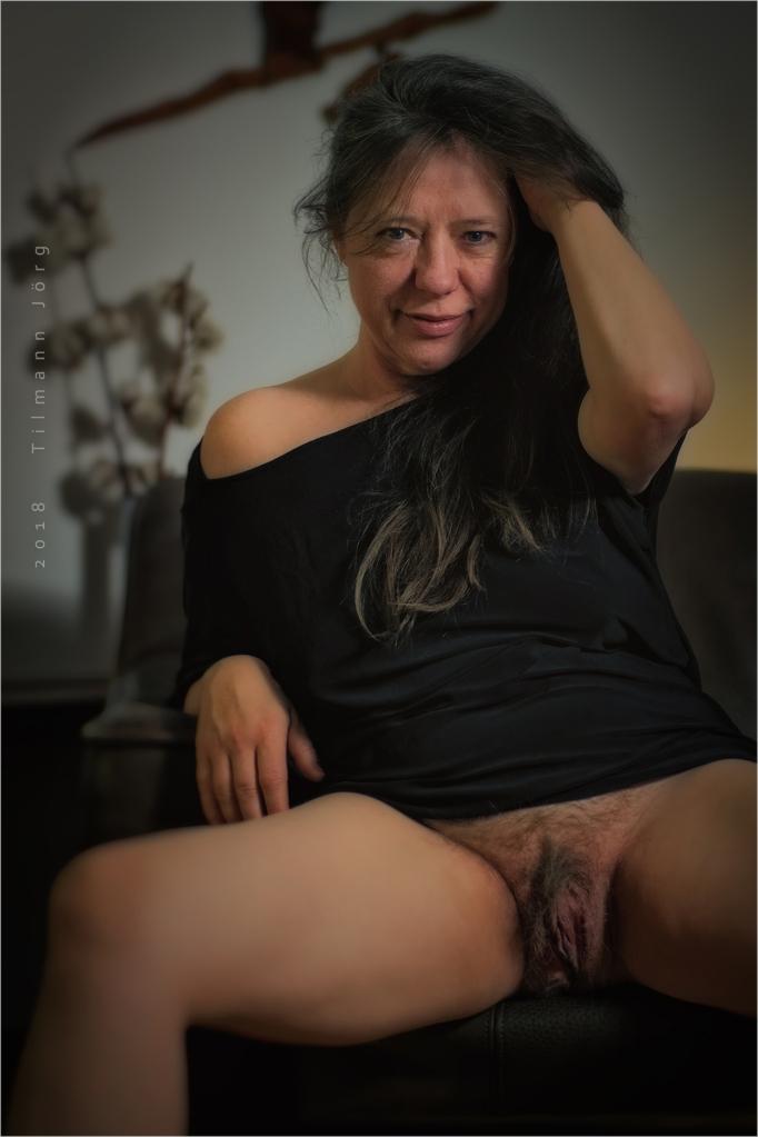 halbnackte Frau sitzt auf dem Sofa und zeigt ihre Vulva