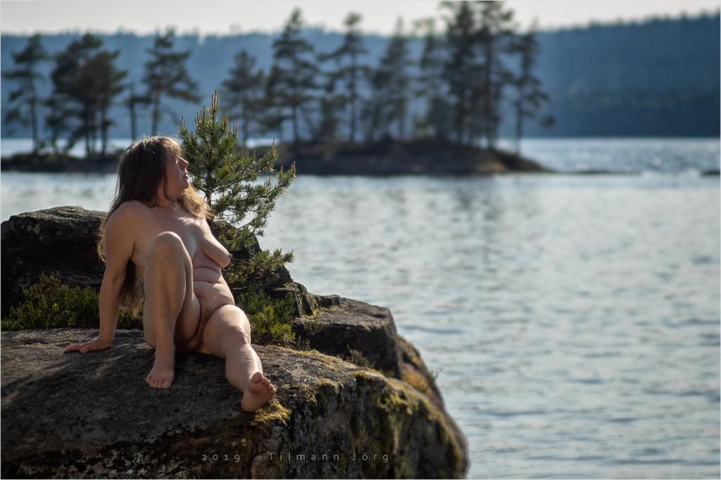 nackte frau auf einem felsen im See
