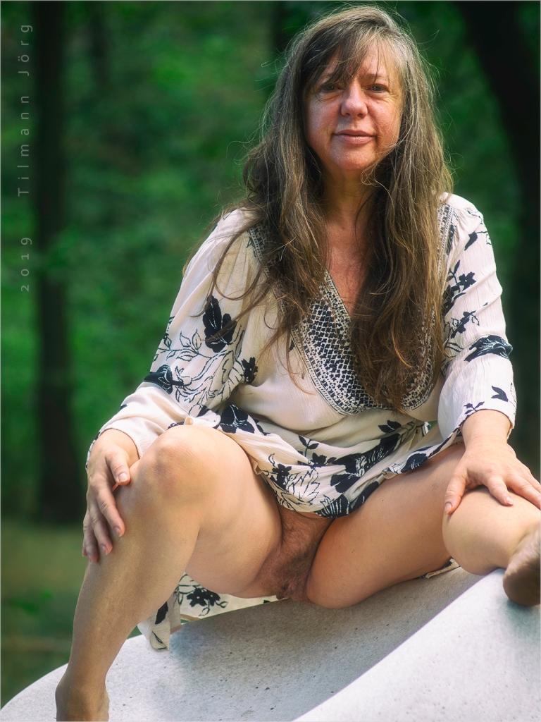 nackte Frau auf einem großen Sitzkiesel