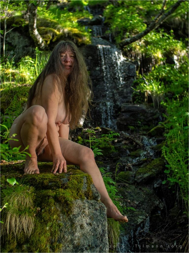 Nackte Frau im Wald vor einem Wasserfall