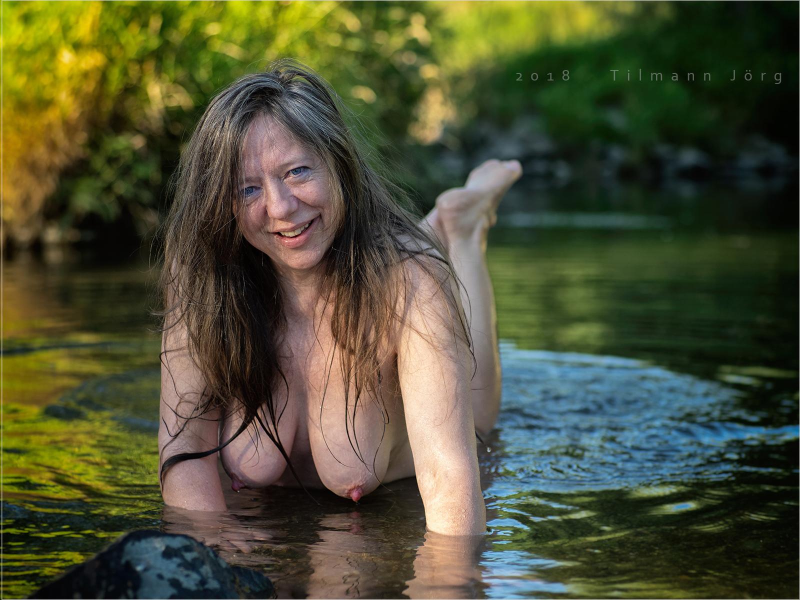 Nackte Frau liegt im Fluss und lacht