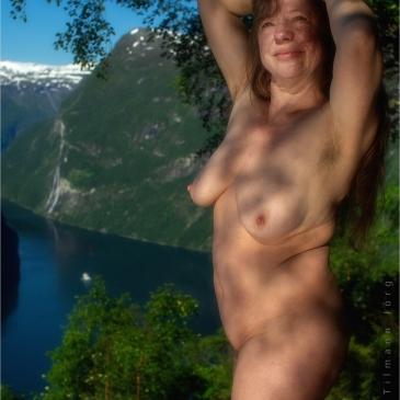 Nackte Frau vor dem Geirangerfjord mit Fährschiff