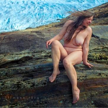 Nackte Frau vor einer Gletscherzunge