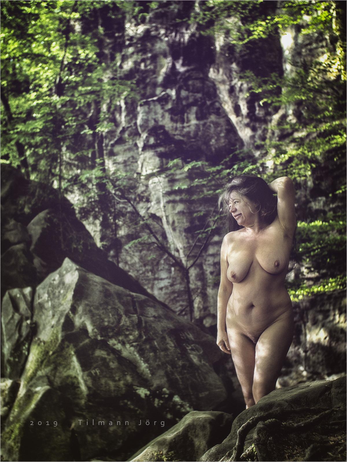 nackte Frau vor einer Felswand