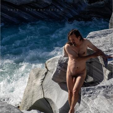 männlicher Akt vor tobendem Wasser